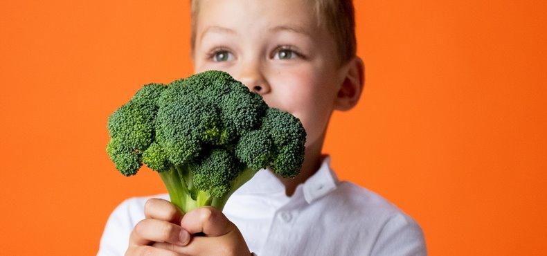 Dečak drži brokoli ispred narandžaste pozadine